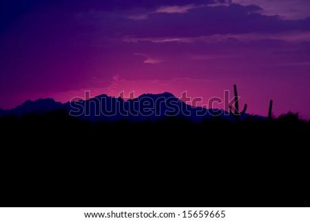 Pink & blue desert sunset over mountain range - stock photo