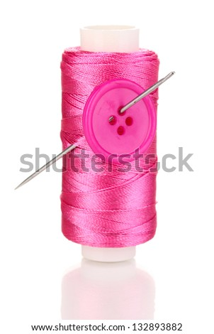 Pink bobbin with needle and buttons isolated on white - stock photo