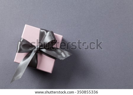 Pink box with gray ribbon and bow on a gray background - stock photo