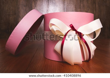 Pink box with ribbon on a wooden background