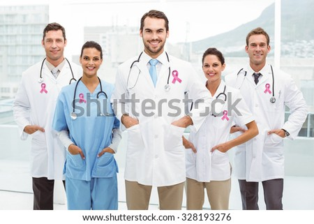 Pink breast cancer awareness ribbon against confident doctors with hands in pockets - stock photo