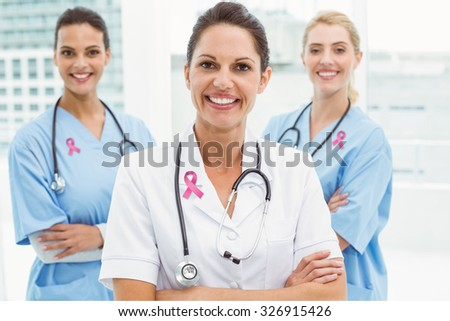 Pink breast cancer awareness ribbon against portrait of confident female doctors with arms crossed - stock photo
