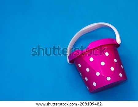 pink bucket with white dots in the water - stock photo