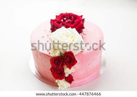 Pink cake decorated with white and burgundy roses - stock photo