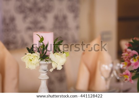 Pink candle and flower composition on the table in the restaurant