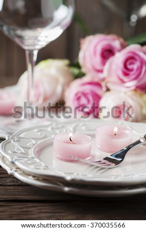 Pink candle and roses on the table, selective focus