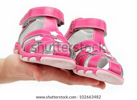 Pink Children's sandals in the women's hand isolated on white.