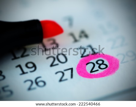 Pink circle. Mark on the calendar at 28. - stock photo