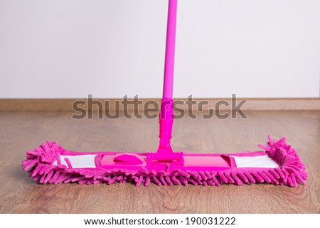 pink cleaning mop on wooden parquet floor - stock photo