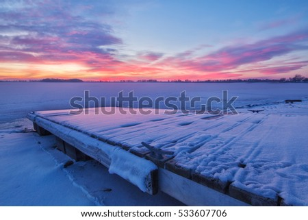 Pink Clouds form over a Colorado Lake and the fishing dock on a very cold winter's morning