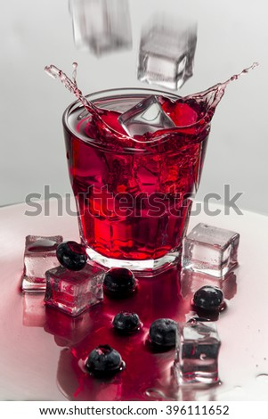 Pink cocktail is going to splash. Ice cubes hit cocktail's surface. Glass with tasty liquid on a clear background. - stock photo