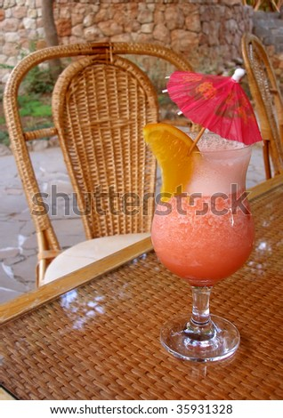 pink cocktail on the wattled table - stock photo
