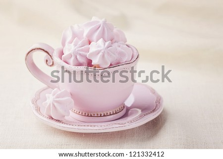 Pink colored meringue in a teacup - stock photo