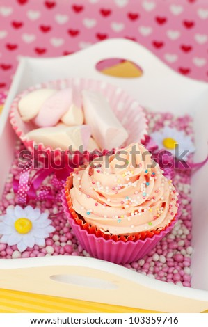 pink cupcake with marshmallows on a plateau with hearts background - stock photo