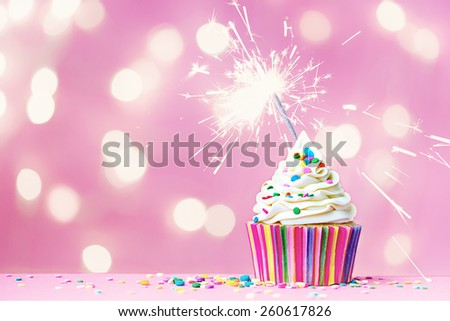 Pink cupcake with sparkler and fairy lights - stock photo