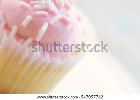 Pink cupcake with white sprinkles in horizontal format with extremely shallow depth of field.  Room for your text.