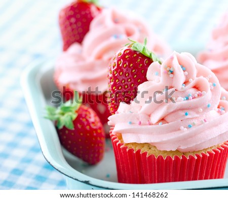 Pink cupcakes with fresh strawberries and sprinkles on a vintage tray and blue retro towel - stock photo