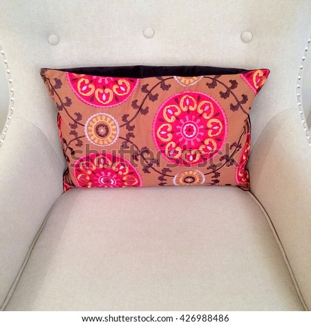 Pink cushion with floral design decorating white armchair. - stock photo