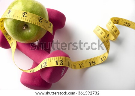 Pink dumbbells with apple and tape measure. Concept health, diet and sports. Horizontal composition. Top view