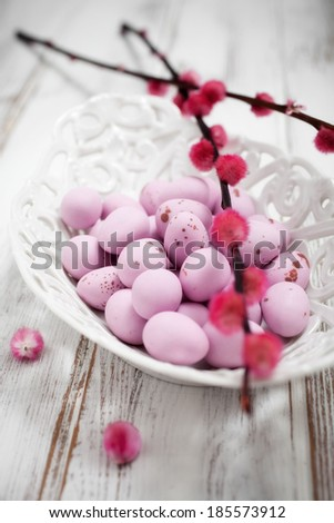 Pink Easter chocolate eggs in white bowl - stock photo
