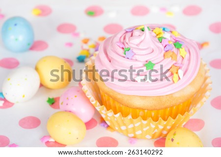 Pink Easter cupcake with candy and sprinkles, shallow depth of field - stock photo