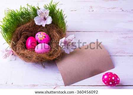pink Easter eggs in a nest with white flowers in the green fresh grass on the white wooden background with natural unbleached paper for congratulation. Easter background. Easter symbol. Copy space - stock photo