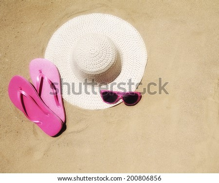 pink flip flop sandals, a hat and sunglasses - stock photo