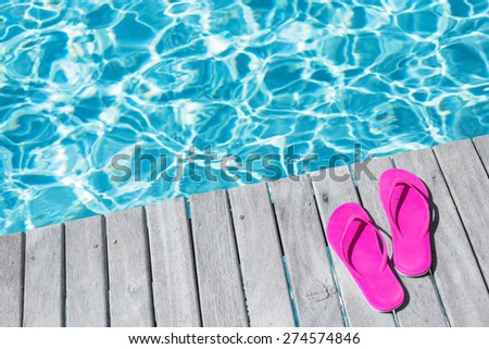 Pink flip flops by the swimming pool - stock photo