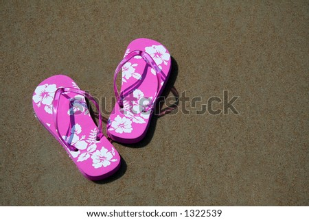 Pink flip-flops on the sand at the beach - stock photo