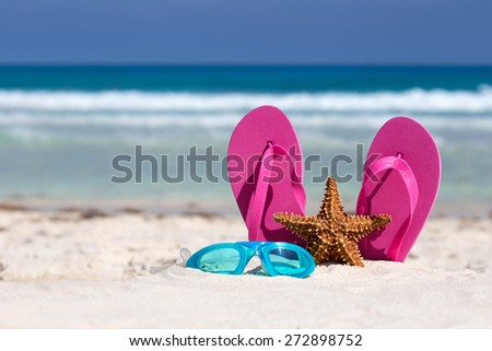 Pink flip flops, swimming glasses and starfish on white sandy beach. Summer vacation concept  - stock photo