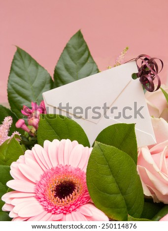 Pink flower bouquet with greeting card in envelope - stock photo