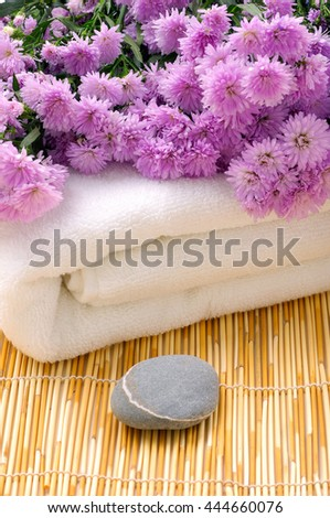 Pink flower on towel with stone on mat  - stock photo
