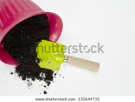 Pink flower pot with soil spilled and garden shovel tipped over isolated on white background