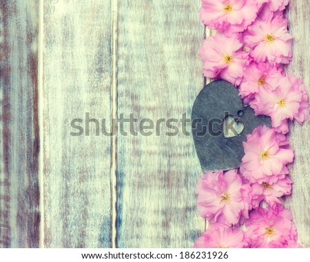 pink flowers and heart on the wooden background