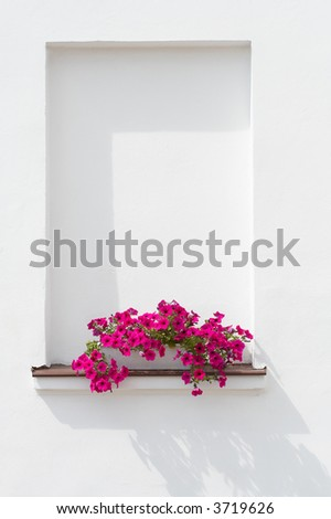 Pink flowers in basket standing at windowsill against white wall. - stock photo