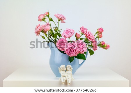 Pink flowers in blue jug. Roses in jug. Two angels.