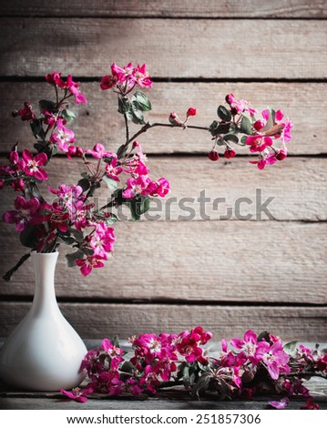 pink flowers in vase on wooden background