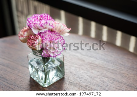 pink flowers in vase on wooden table decoration - stock photo