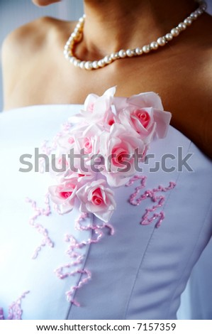 Pink flowers on the beautiful bride dress. Bride with necklace - stock photo