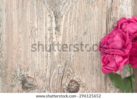 Pink flowers roses on rustic wooden background with copy space for greeting message. Mother's Day background concept