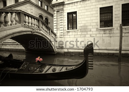 Pink flowers waiting on a rain covered gondola in Venice, Italy. - stock photo