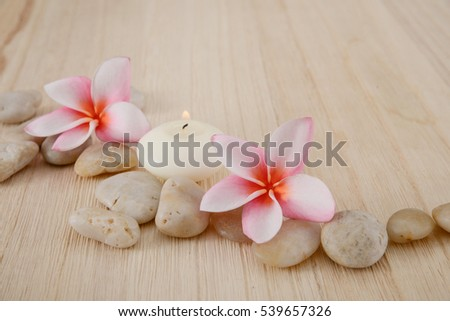 Pink Frangipani flower with pebbles ,candle on wooden background