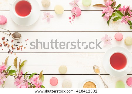 Pink fruity tea and pastel french macarons cakes on rustic white wooden background. Dessert in a garden. Flat lay composition (from above, top view). Free text space. - stock photo