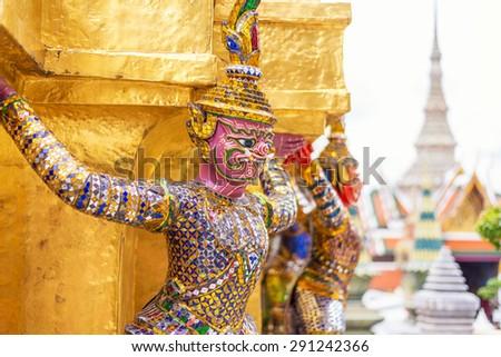 Pink Giants statue under golden pagoda in wat pra keaw , Bangkok , Thailand - stock photo