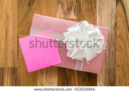 Pink gift box and paper note on wooden background - stock photo