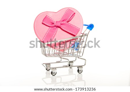 pink gift box in steel shopping cart on white background