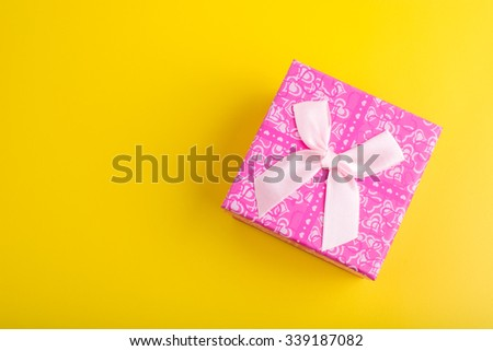 Pink gift box on yellow background, Top view - stock photo