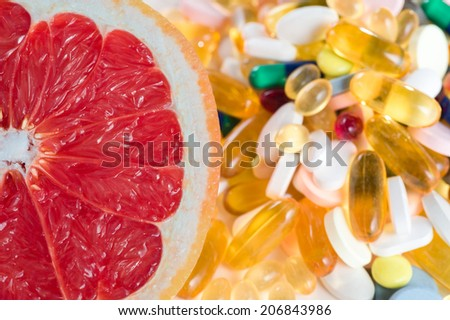 Pink grapefruit and pills, vitamin supplements on white background, healthy diet concept - stock photo