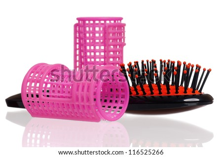 Pink hair curlers and hairbrush isolated on white background - stock photo