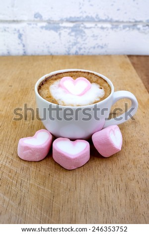 Pink heart marshmallow on latte cofee for valentine's day with old wood background. - stock photo